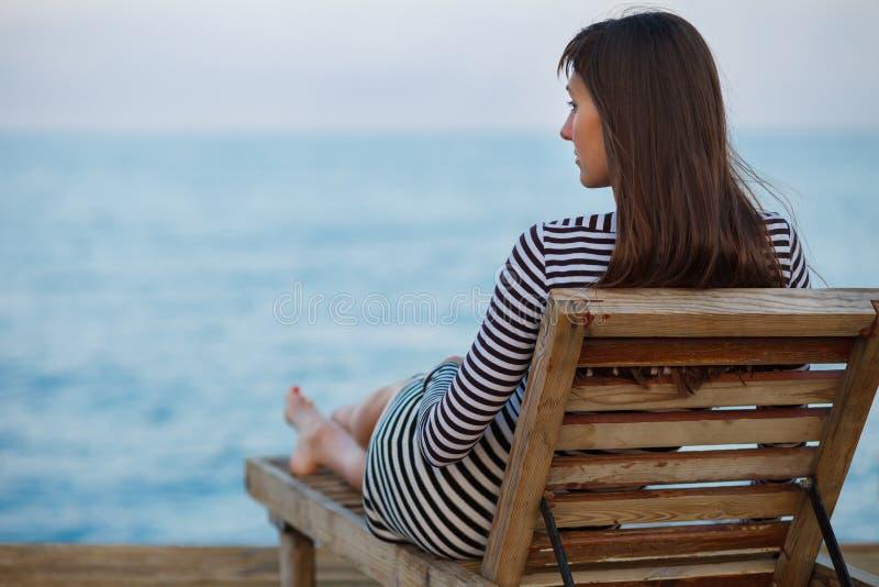 Openluchtportrit van het mooie jonge vrouw ontspannen bij de zeekust bij de avond stock foto