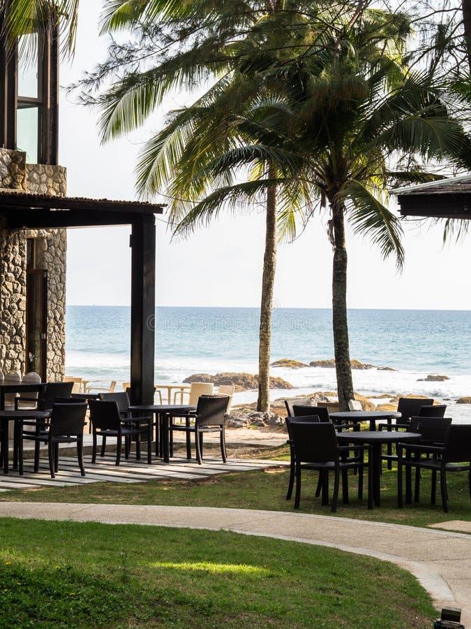 Openluchtrestaurant met lijsten en stoelen in de open plek onder de palmen tegen het blauwe kalme overzees en het zandige strand  stock afbeeldingen