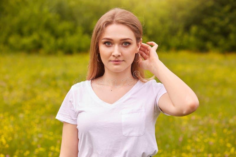 Openluchtschot die van het aantrekkelijke jonge mooie slanke meisje van het blondehaar, het toevallige T-shirt stellen in openluc royalty-vrije stock afbeeldingen
