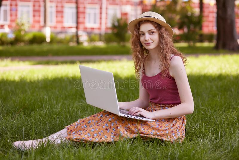 Openluchtschot die van het knappe charmante model stellen op gras in park, kleurrijke rok, rode bovenkant en strohoed dragen, die royalty-vrije stock afbeeldingen