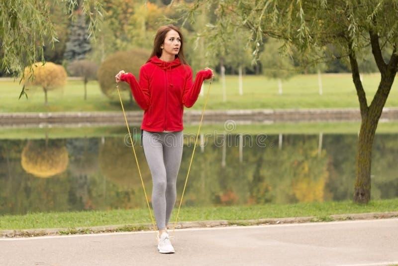 Openluchtschot van geconcentreerde jonge vrouw met springtouw in openlucht in aard Geschiktheidswijfje die met springtouw in een  stock foto