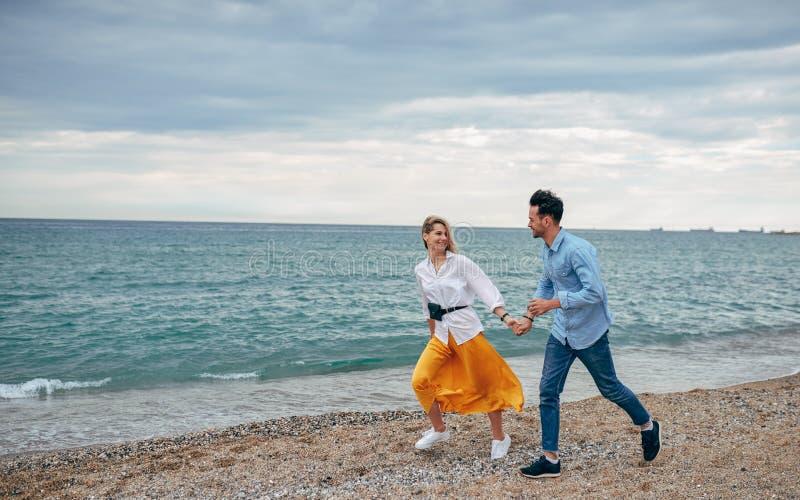 Openluchtschot van gelukkig glimlachend paar die op strand lopen Jonge knappe man en mooie vrouw die samen op kust wandelen stock afbeeldingen