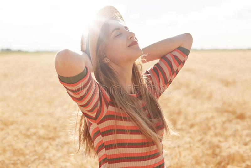 Openluchtschot van gelukkige jonge vrouw die in gestreepte uitrusting en zonhoed van zon op graangewassengebied genieten, het vro royalty-vrije stock foto's