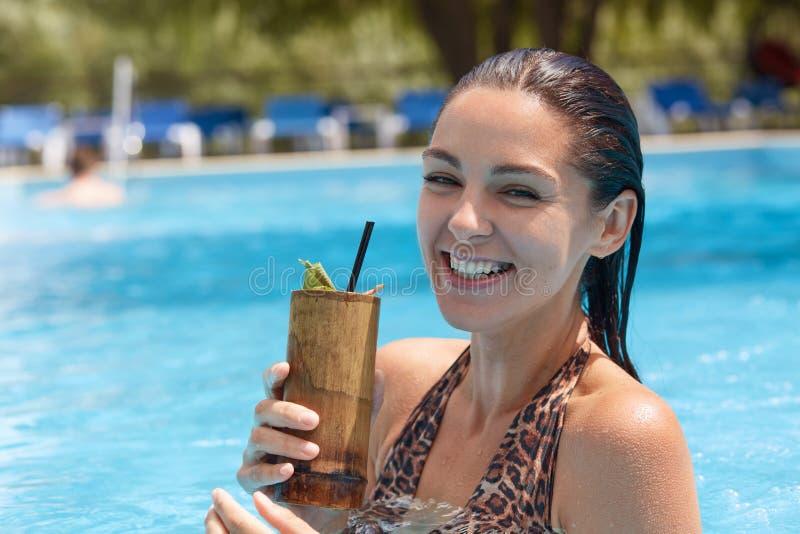 Openluchtschot van grappige vrolijke vrouw die houten glas met cocktail houden, direct bekijkend camera, oprecht lachend, het dra stock foto