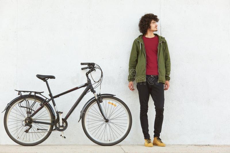 Openluchtschot van slanke lange hipsterkerel die einde met zijn fiets hebben, die het berijden reis nemen, die dierbaar van actie stock afbeeldingen