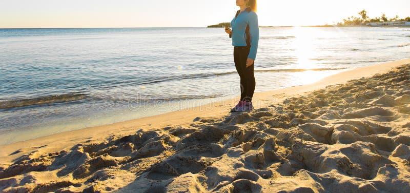 Openluchtsport, fitness gadget en mensenconcept - Close-up van vrouwelijke fitness holdingssmartphone met oortelefoons stock fotografie