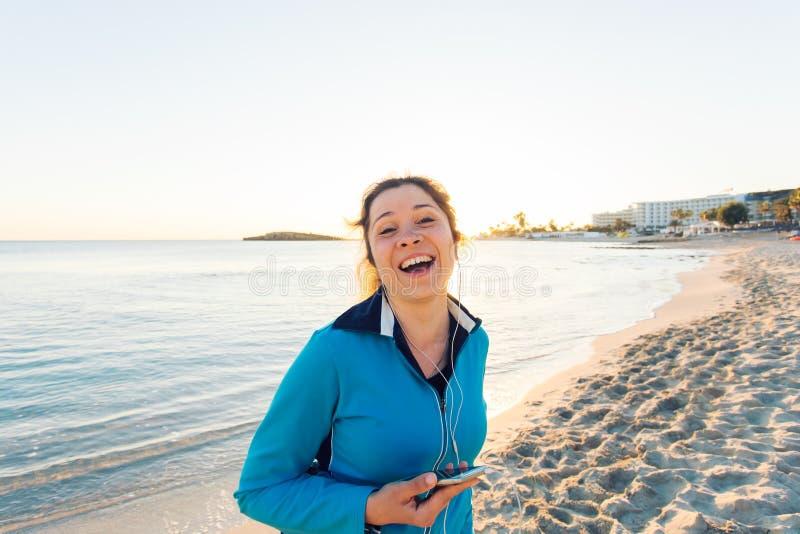 Openluchtsport, fitness gadget en mensenconcept - het Glimlachen vrouwelijke fitness holdingssmartphone met oortelefoons royalty-vrije stock afbeeldingen