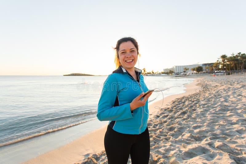 Openluchtsport, fitness gadget en mensenconcept - het Glimlachen vrouwelijke fitness holdingssmartphone met oortelefoons royalty-vrije stock fotografie