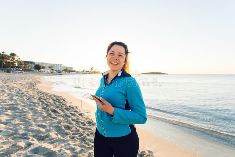Openluchtsport, fitness gadget en mensenconcept - het Glimlachen vrouwelijke fitness holdingssmartphone met oortelefoons royalty-vrije stock afbeelding