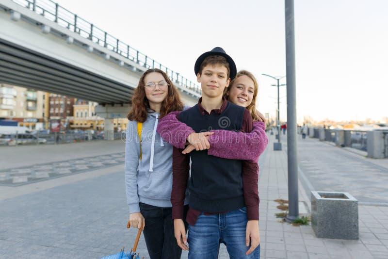 Openluchtstadsportret van drie jongens en meisjes 13, 14 jaar van de vriendentiener oud stock fotografie