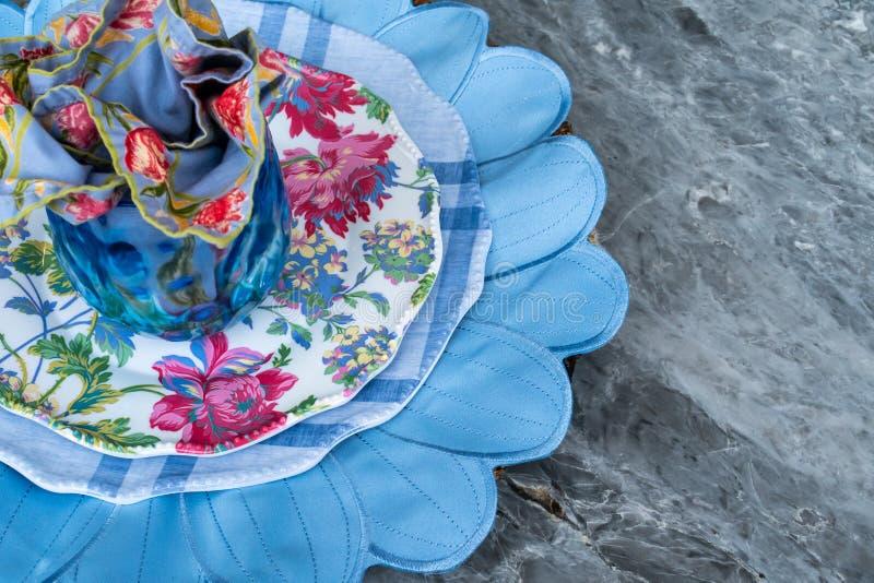 Openluchtterras die dineren: koele blauwe tonen, het onderleggertje van het bloembloemblaadje, het bloemen napking en platen stock fotografie