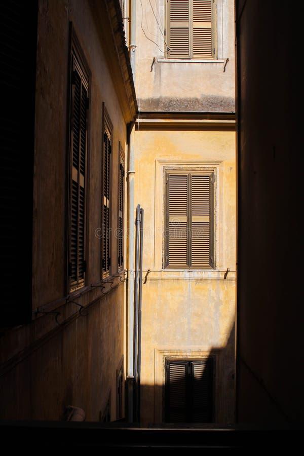 Openluchtvenstermening van een warm zonovergoten generisch gebouw, in Rome Italië stock fotografie