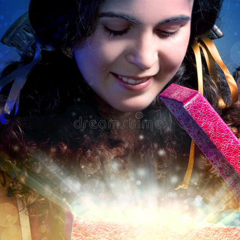 Opens a Christmas magic gift. Beautiful young girl opens a Christmas magic gift royalty free stock image