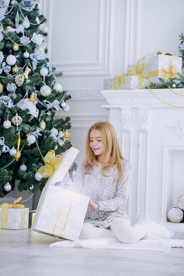 Opens gift box. Pretty nine year old girl opens a gift box and surprises. Luxurious apartments decorated for Christmas. Merry Christmas and Happy New Year royalty free stock images