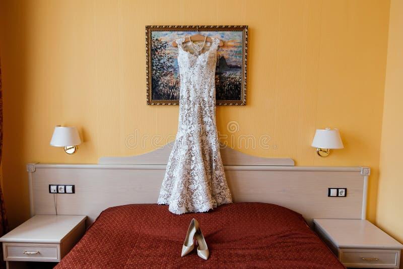 Openwork Hochzeitskleid, das am Bild nahe der Wand nahe bei den Braut ` s Schuhen auf dem Bett im Braut ` s Schlafzimmer hängt lizenzfreie stockbilder