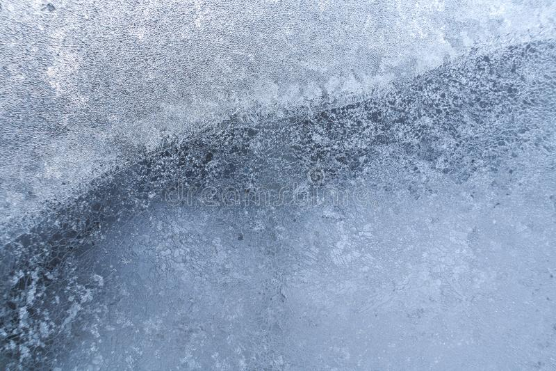 Openwork icy drawing on frozen window glass as background or wallpaper. Natural winter background stock photography