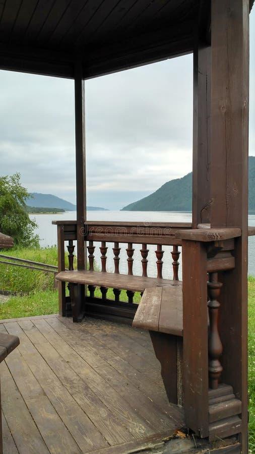 Openwork rzeźbiąca drewniana pergola, alkierz, altanka, pawilon na banku rzeka na chmurnym dniu zdjęcia stock