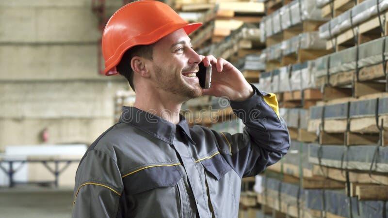 Operário feliz em uma fala de sorriso do capacete de segurança no telefone imagem de stock royalty free