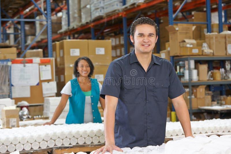 Operário que verifica bens na linha de produção foto de stock royalty free