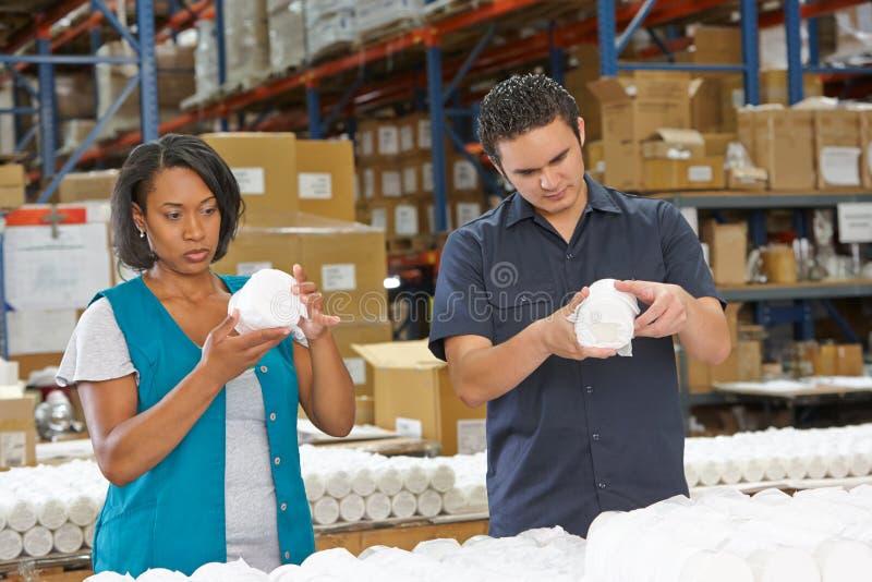 Operários que verificam bens na linha de produção imagem de stock