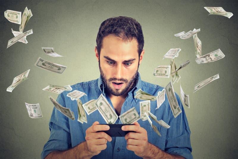 Operação bancária em linha, conceito do comércio eletrônico Homem chocado que usa o smartphone foto de stock royalty free