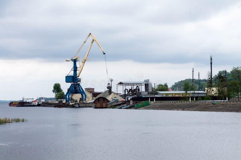 Operação do recipiente na porta O guindaste de levantamento derrama a areia no porto fluvial indústrias foto de stock royalty free