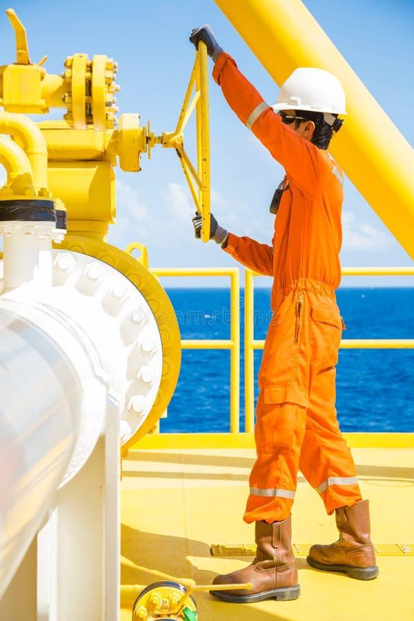 Operaciones costeras del petróleo y gas, válvula abierta del operador de la producción para permitir el gas que fluye a la línea  foto de archivo libre de regalías