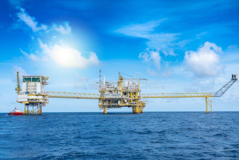 Operaciones de petróleo y gas mar adentro, descarga de carga en la plataforma central de procesamiento mar adentro por barco de s foto de archivo libre de regalías