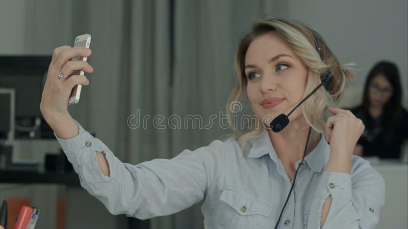 Operador bonito de la llamada que toma selfies del teléfono mientras que habla con el cliente imagen de archivo