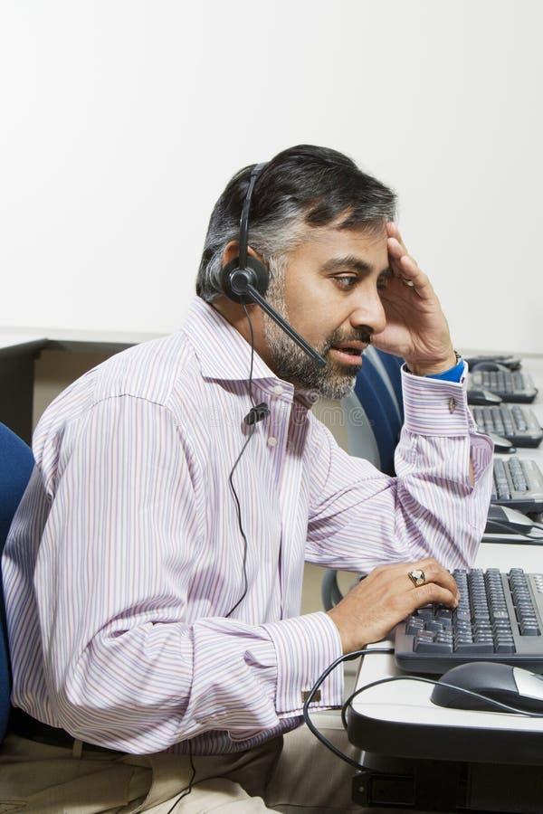 Operador cansado del servicio de atención al cliente en llamada imagen de archivo libre de regalías