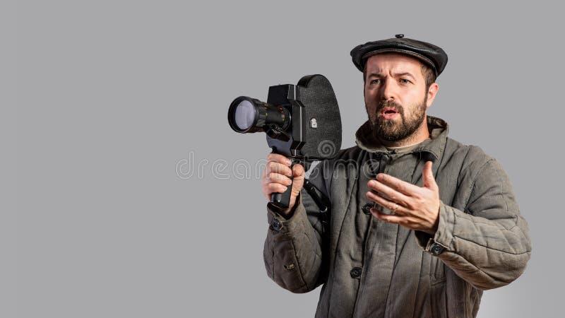 Operador cinematográfico emocional com a câmera retro em suas mãos, tiro do estúdio Estilo antiquado da roupa Olhar cômico Concei fotografia de stock