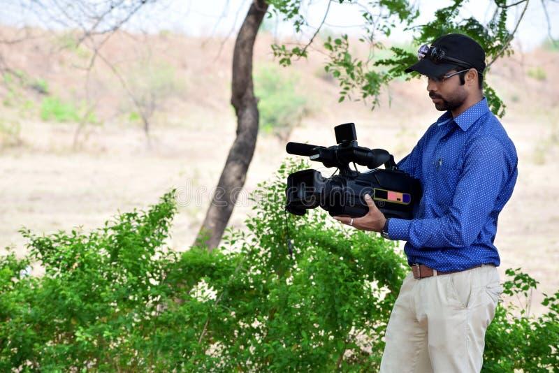Operador cinematográfico que usa um documentário exterior do película da câmara de vídeo profissional, foco na câmera fotos de stock royalty free