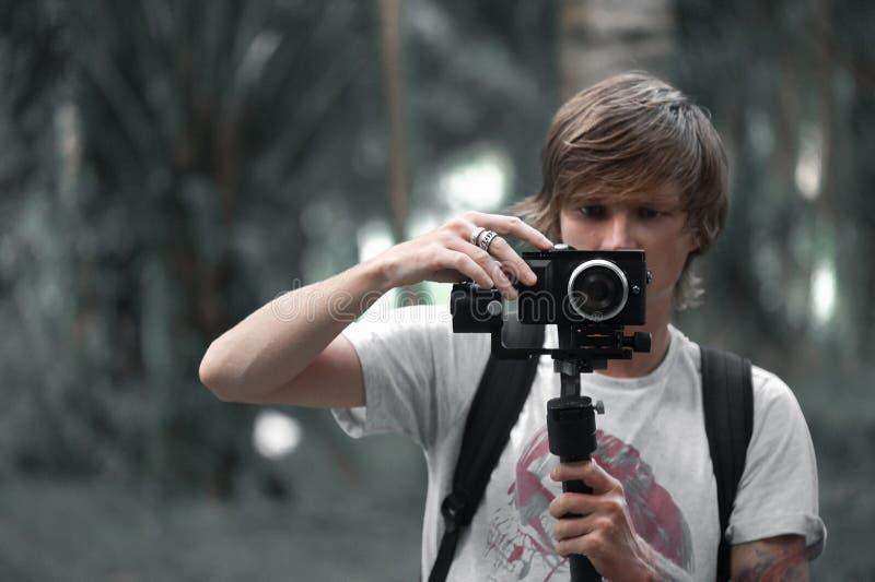 Operador da câmara de vídeo que trabalha com seu equipamento imagem de stock