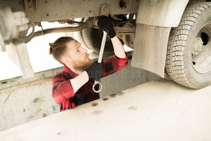 Operador da garagem que repara o caminhão foto de stock