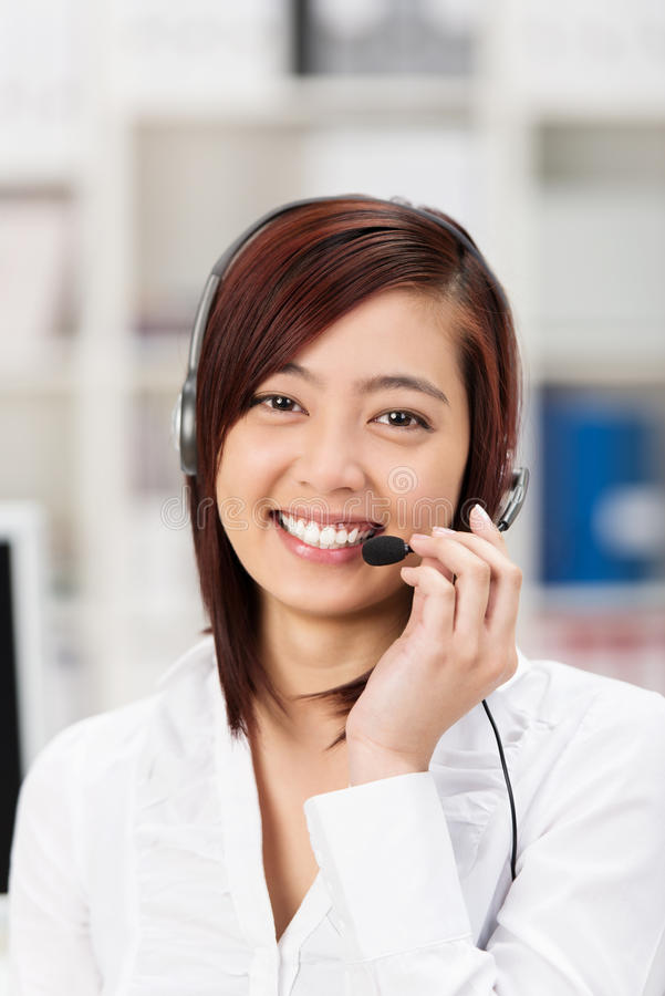 Operador de centro asiático joven amistoso feliz de llamada foto de archivo