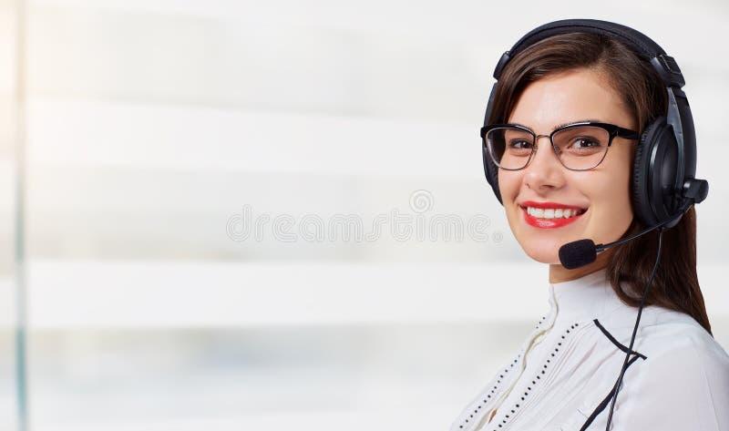 Operador de centro de atención telefónica de la mujer joven en auriculares en fondo de la oficina fotografía de archivo