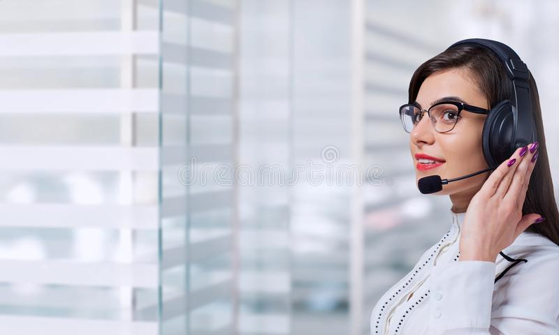Operador de centro de atendimento da jovem mulher nos auriculares no escritório para negócios b imagem de stock royalty free