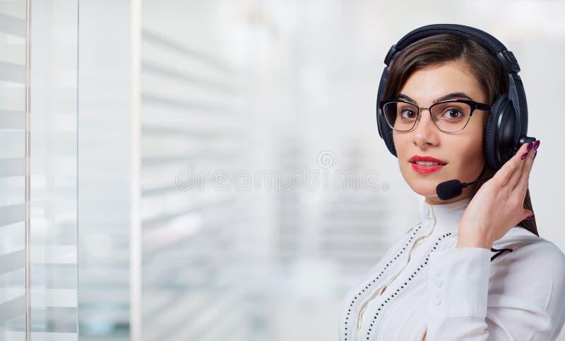 Operador de centro de atendimento da jovem mulher nos auriculares no fundo do escritório imagem de stock royalty free