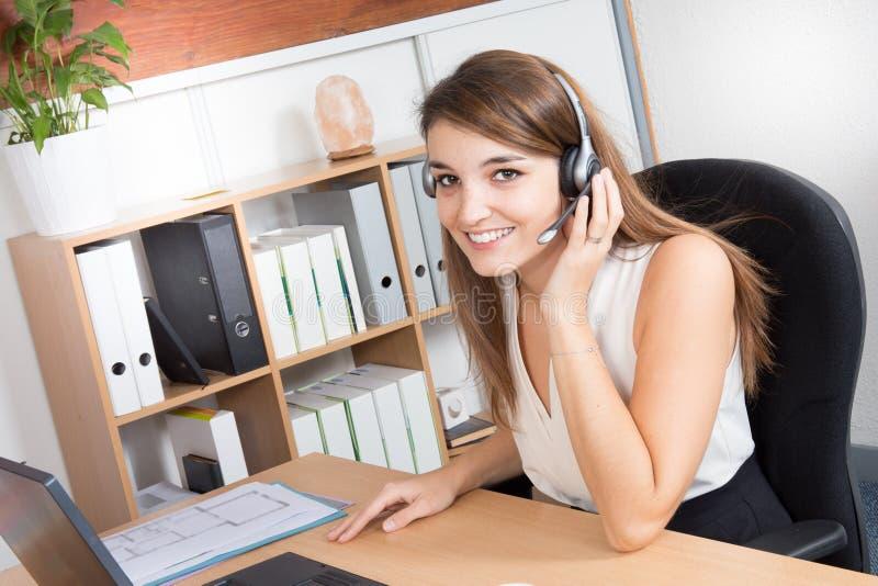 Operador de centro atrativo feliz da chamada da jovem mulher ou auriculares vestindo da menina do recepcionista fotografia de stock royalty free