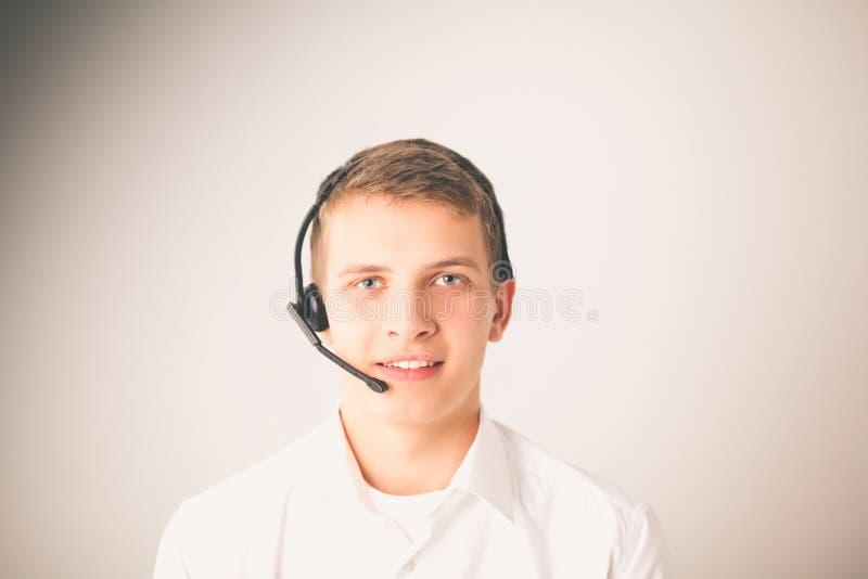 Operador de la atención al cliente con auriculares en el fondo blanco imagen de archivo