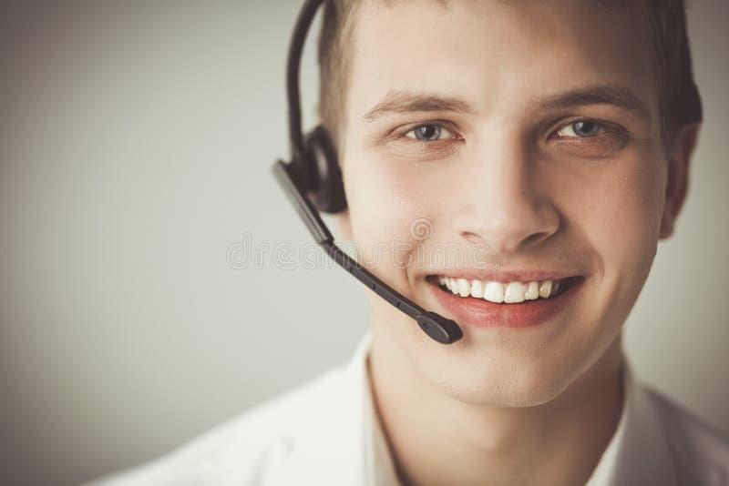 Operador de la atención al cliente con auriculares en el fondo blanco fotografía de archivo