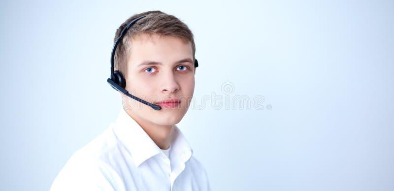 Operador de la atención al cliente con auriculares en el fondo blanco foto de archivo