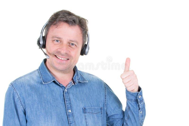 Operador de la ayuda del hombre del cliente con los thulbs de las auriculares para arriba en el fondo blanco imagenes de archivo