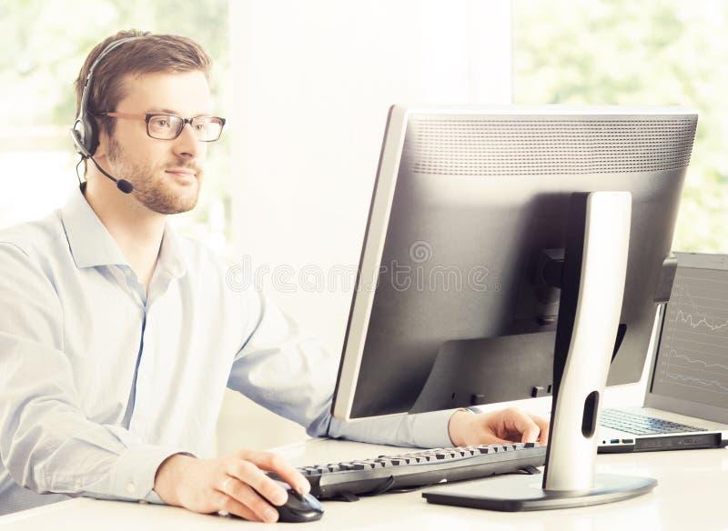 Operador de la ayuda en el trabajo en un centro de atención telefónica imagen de archivo