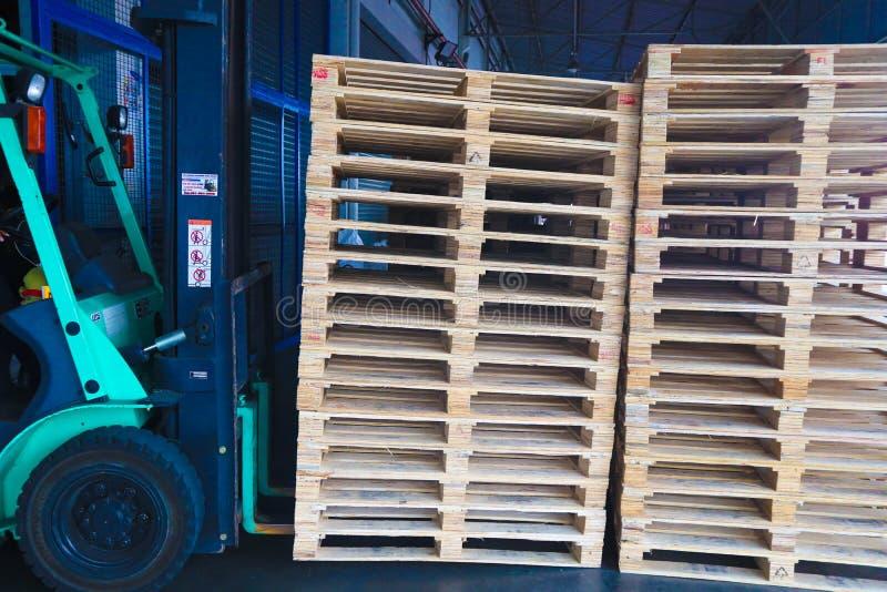 Operador de la carretilla elevadora que maneja las plataformas de madera en el cargo del almac?n para el transporte a la f?brica  imagen de archivo libre de regalías