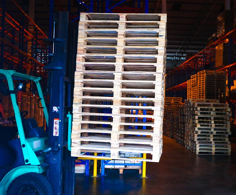 Operador de la carretilla elevadora que maneja las plataformas de madera en el cargo del almac?n para el transporte a la f?brica  fotografía de archivo libre de regalías