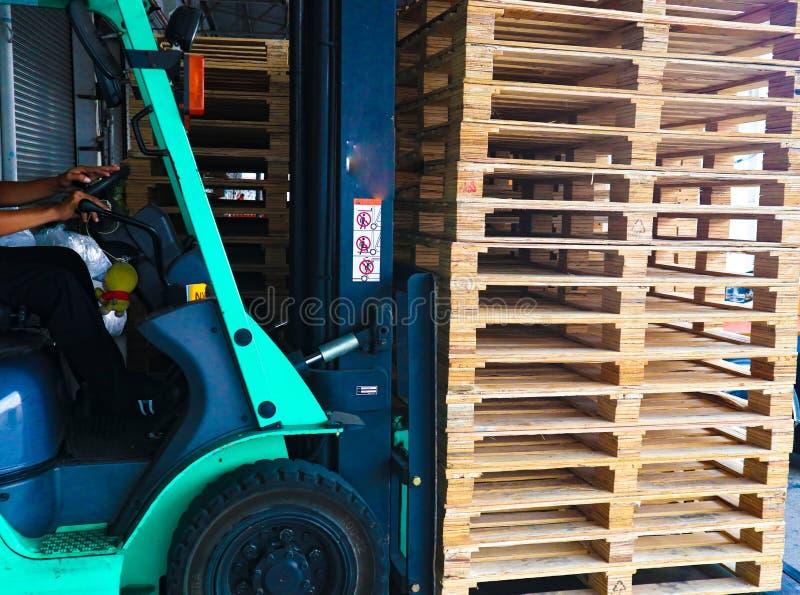 Operador de la carretilla elevadora que maneja las plataformas de madera en el cargo del almac?n para el transporte a la f?brica  imagen de archivo