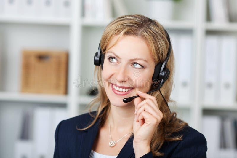 Operador de sexo femenino del servicio de atención al cliente que usa las auriculares imagenes de archivo