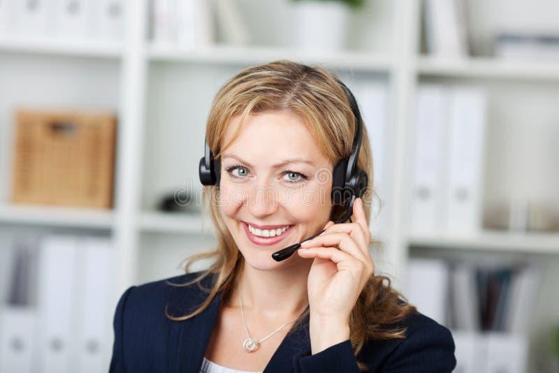 Operador de sexo femenino del servicio de atención al cliente que usa las auriculares en oficina imagenes de archivo