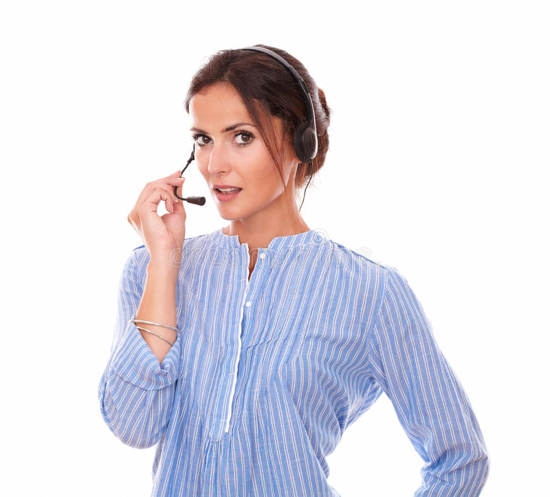 Operador de sexo femenino encantador que habla con el auricular foto de archivo